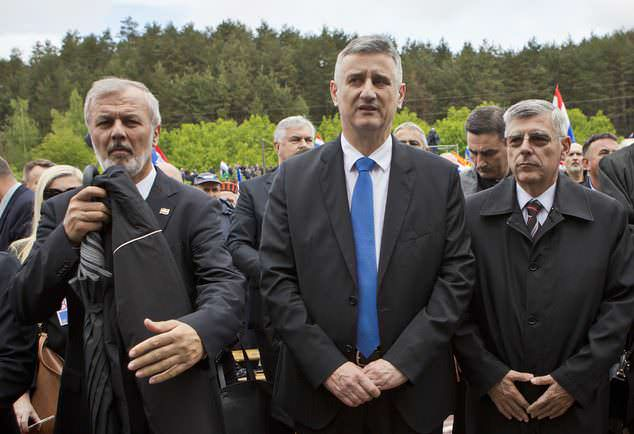 Croatia's deputy prime minister Tomislav Karamarko, center, parliament speaker Zeljko Reiner, right and head of a county Ante Sanader attend a mass in Bleiburg, Austria, Saturday, May 14, 2016.  Thousands of far-right supporters have gathered on a field in southern Austria to commemorate the massacre of Croatian pro-Nazis by victorious communists at the end of World War II. The event on Saturday, which featured insignia and flags of Croatia's wartime pro-fascist Ustasha regime, comes amid a surge of far-right sentiments in the EU's newest member country.  (AP Photo/Darko Bandic)